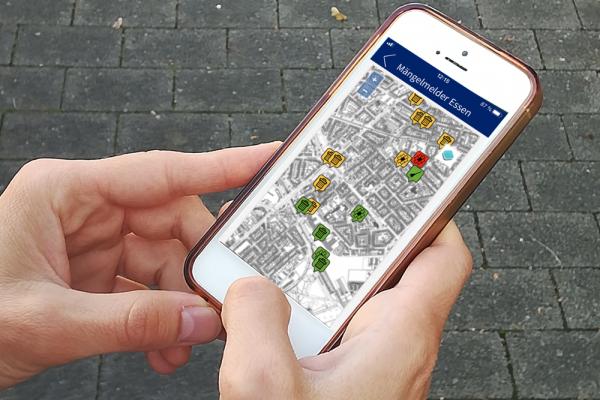 Ein Bürger meldet Straßenschäden mobil mit dem Mängelmelder Essen