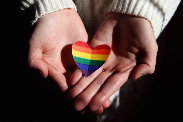 Zwei Hände mit einem Herz in Regenbogenfarben. Symbolbild für Toleranz und Solidarität. Für die Opfer des § 175 StGB soll nun in Darmstadt ein Mahnmal errichtet werden, das ebenso ein Zeichen für Toleranz sein soll. Über Entwürfe für das Mahnmal können die Bürger nun abstimmen.
