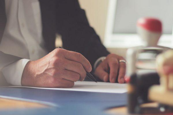 Person am Schreibtisch in einer Verwaltung. Symbolbild für die Umfrage und Evaluation zur bürgernahen Sprache in der Finanzverwaltung. Diese hat die Oberfinanzdirektion NRW im Sommer 2020 im Kooperation mit der wer denkt was GmbH durchgeführt.